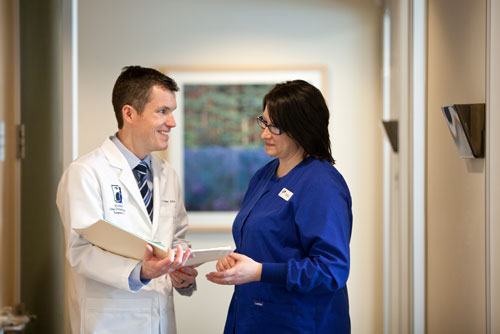 Dr. Hoyer speaking with a staff member at Madison Oral Surgery & Dental Implants in Madison, WI